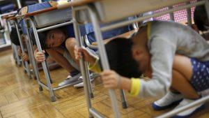 Trẻ em núp dưới ngăn bàn để tránh động đất.